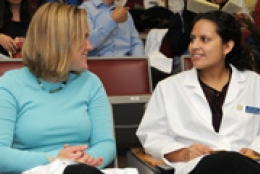 two female students, one in lab coat, looking at each other smiling