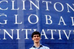 Student standing in front of a Clinton Global Initiative banner