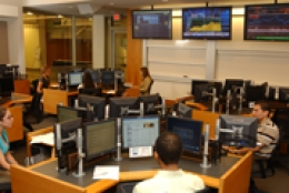 students sitting in rooms with multiple computer screens in front of them