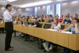 students sitting in classroom listening to a professor who is standing at the front of the room