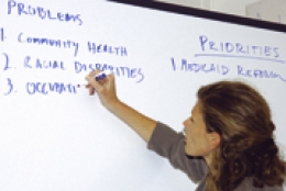 Woman in front of white board writing