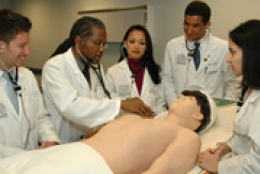 group of students around mannequin with medical tools