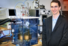 male smiling in lab in front of electrical engineering equipment