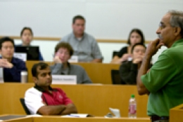 students in classroom with professor teaching at the front of the room