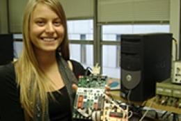 Female student smiling in front of lab equipment